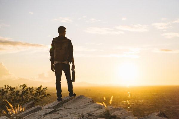 Randonneur regarde le soleil couchant avec ses gourdes de randonnées