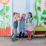 3 enfants heureux qui montrent leurs gourdes